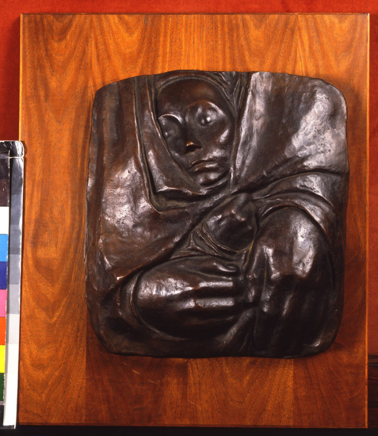 A small face, hands and the suggestion of shoulders form a square bronze relief with rounded corners. The face, on top, looks slightly right, as a pair of hands gather the fabric towards the lower left corner. The fabric folds and creases, forming almost a swirl into the center.