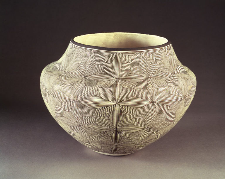 Ceramic jar, featuring a short neck and broad shoulders tapering to a narrow base, is decorated in a geometric, black and white quilt-like pattern. The matte, off-white surface is adorned with geometric, flower-like patterns created by very thin, precisely-placed black lines.
