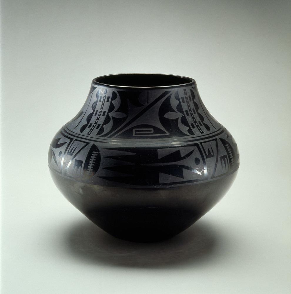 Blackware pottery vessel with a wide mouth and bulbous body that tapers to a narrow base. The pot is adorned with geometric tribal patterns presented in a matte finish on the glossy surface.