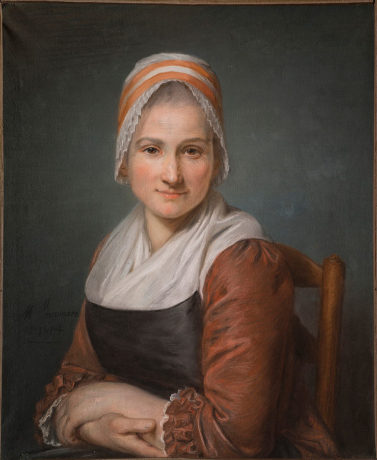 A light-skinned woman with a direct and calm expression sits in a wooden chair, looking straight at the viewer. She wears a dress with red sleeves and a white kerchief that tucks into a blue bodice. Her hair is covered in a white and orange cap that frames her face with lace.