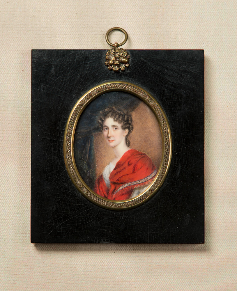 Miniature portrait in an oval frame with gold accents set in a black rectangular pendant depicts a light-skinned woman with brunette ringlets around her face. She wears an embellished red velvet dress and sits in three-quarter pose, gazing out against gray drapery.