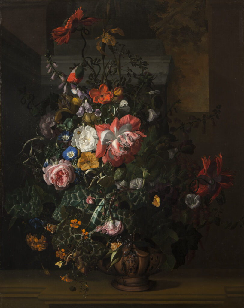 A still life painting featuring an asymmetrical arrangement of flowers; the central section features pink, orange, yellow, and blue flowers and is dramatically highlighted compared to the background and outer edge of arrangement.