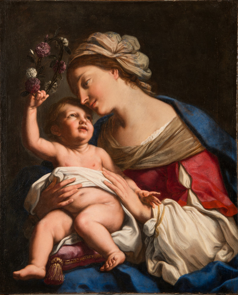 A young, light-skinned, brunette woman gazes down lovingly at the plump baby she holds on her lap. She wears a loose, tan turban, vivid blue cloak, and red dress with white sleeves. The light-skinned child returns her gaze, leaning back to crown the woman with a circlet of roses.