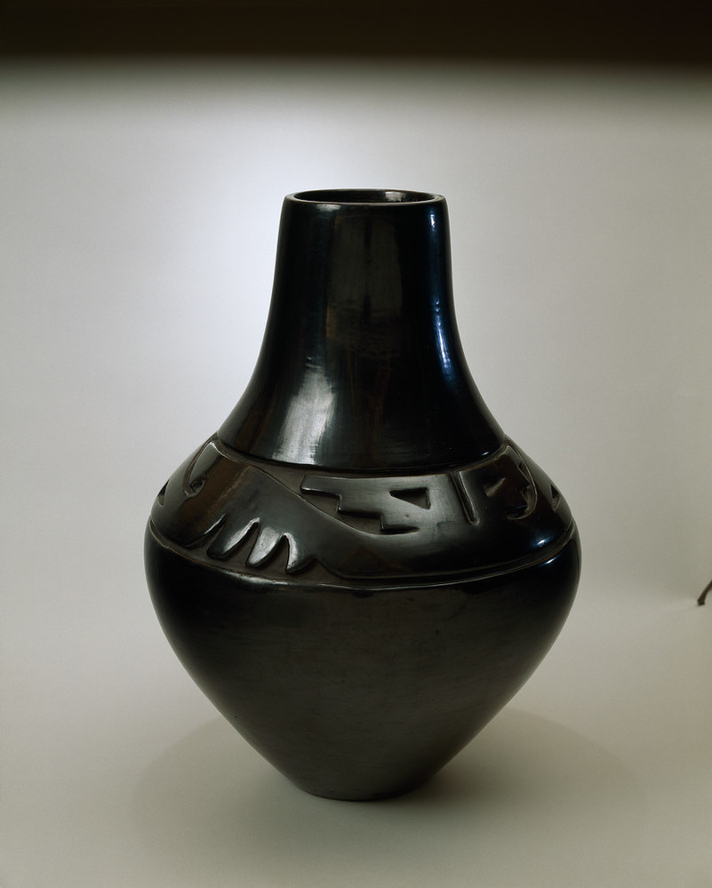 Blackware pottery vessel with tall neck and broad shoulder tapering to a narrow base. The flawless, polished black surface is adorned with deep relief carvings of stylized wings and geometric designs on the shoulder.