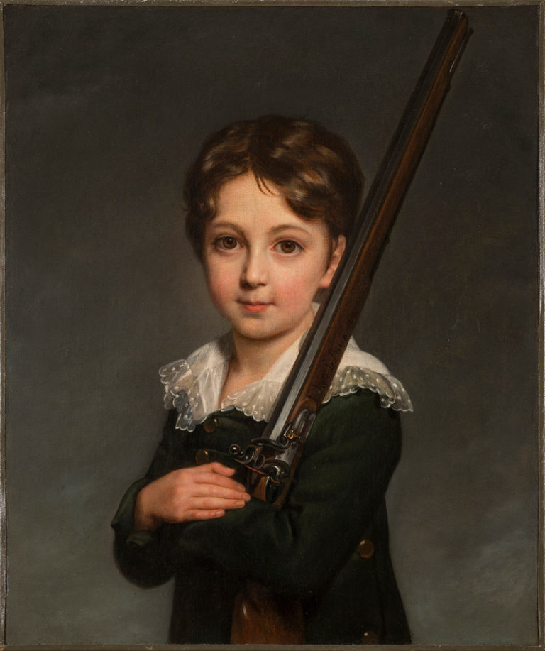 A young boy with light skin and brown hair faces the viewer while cradling the stock of a rifle in his arms and resting the barrel on his left shoulder. He wears a delicate lace collar and is shown against a gray background with visible brushstrokes.