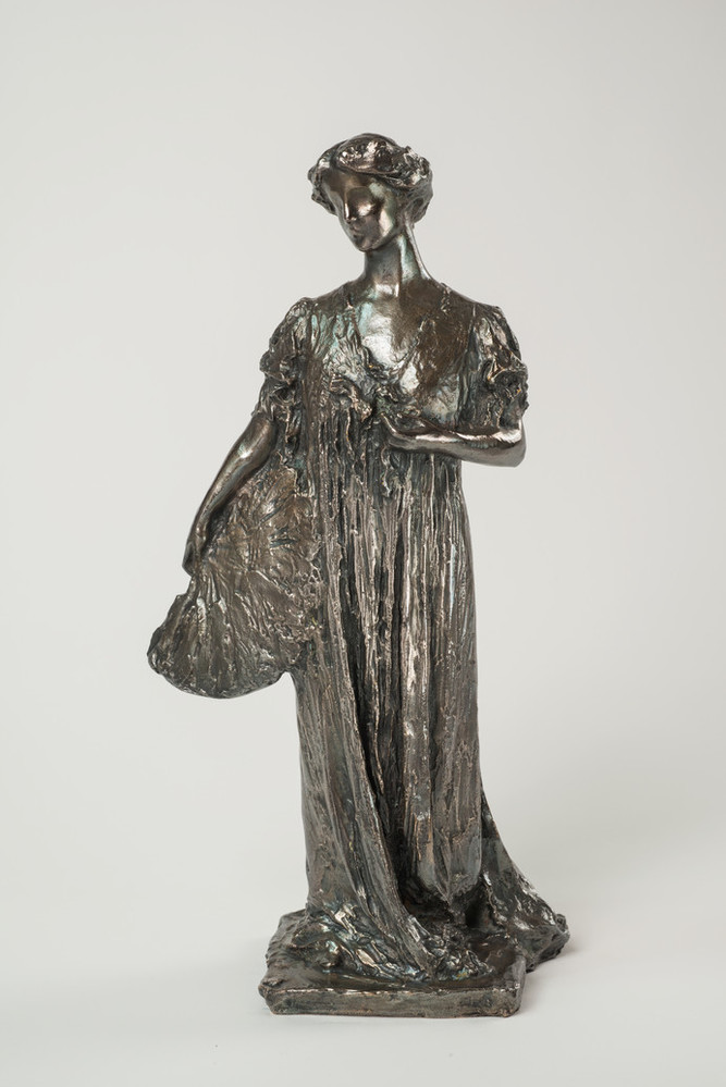 Bronze sculpture of a standing woman gazing over her right shoulder, holding a fan by her side. She wears a long, loose gown that gathers at her feet, with her hair swept off her neck. Her left hand holds a flower by her bust.