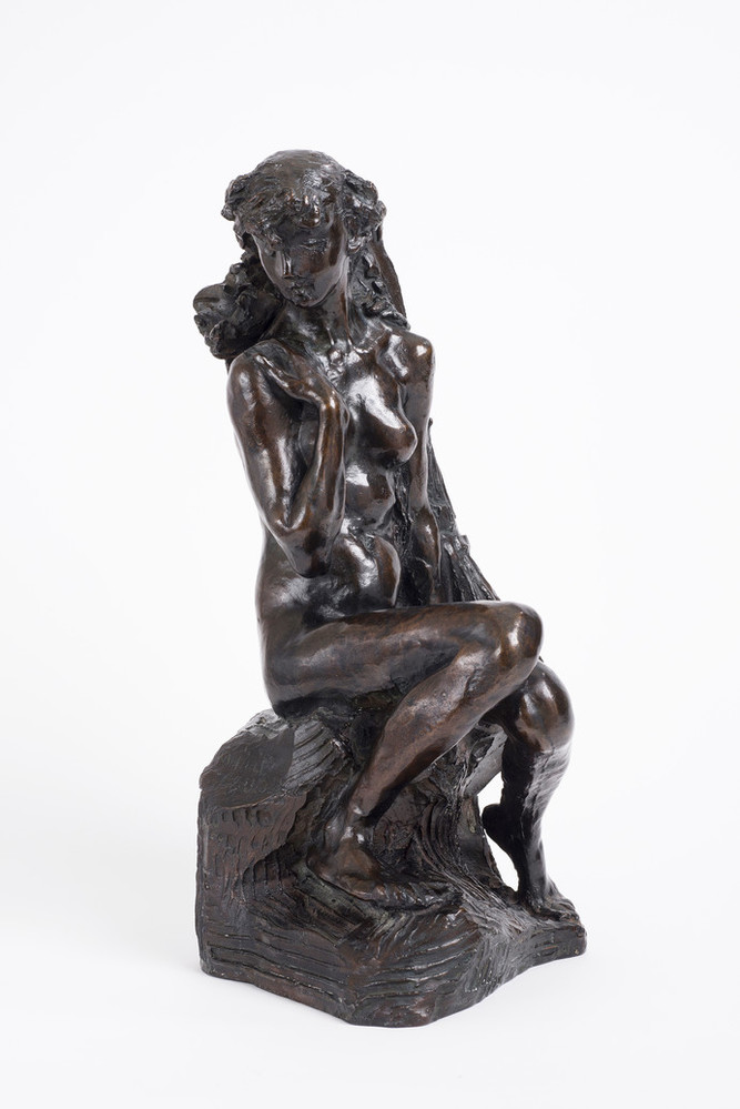 Bronze tabletop sculpture depicting a nude young woman seated on rough-hewn base.leaning against a sheaf of wheat, The figure's knees are drawn together, her left arm hanging at her side and her right arm bent upwards, clasping her shoulder.