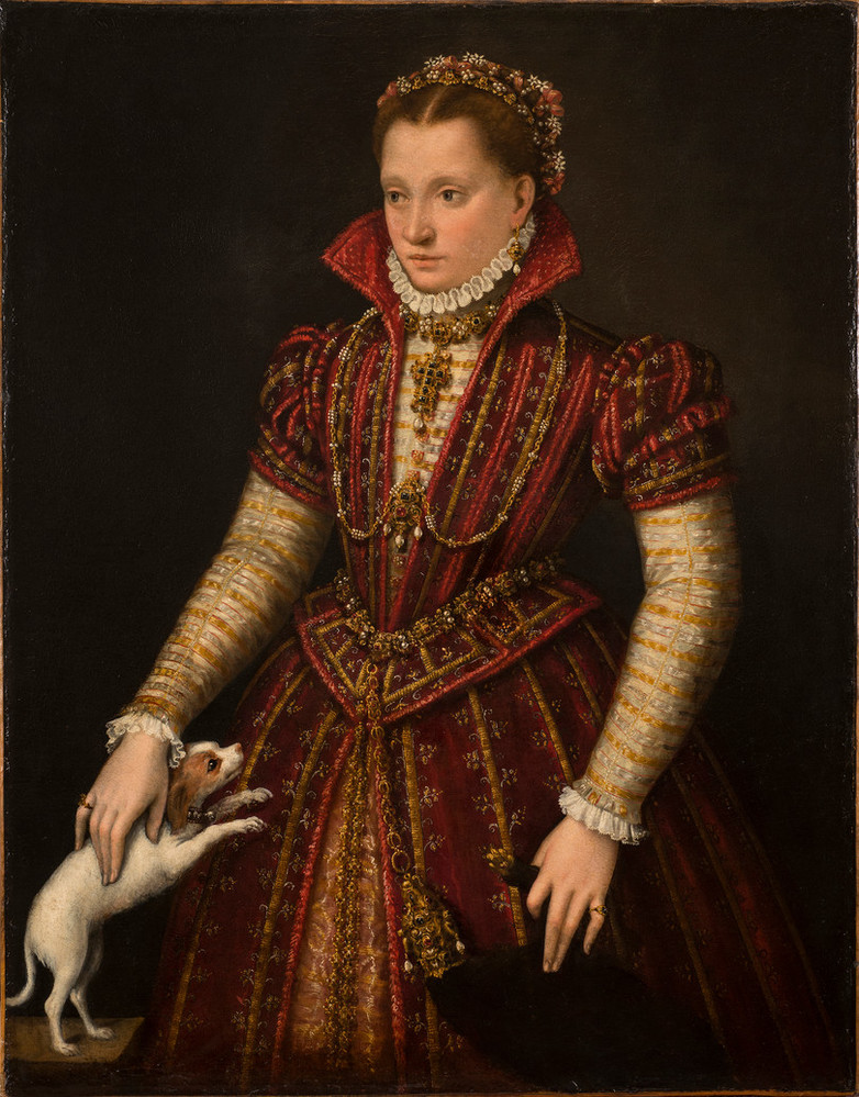 A woman stands in a richly brocaded red dress, her right hand reaching down to pet a small, white dog. Adorned in jewelry, she wears flowers in her hair, parted in the center. The pelt of a small mammal, its head encased in a jeweled holder, hangs from her heavily decorated belt.