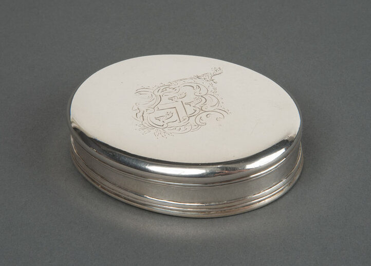 Small oval tobacco box made of silver. The relatively plain box features a Rococo engraving of a coat of arms at the center of the lid.