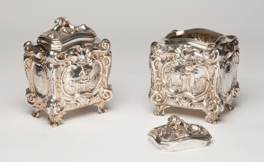 Two silver tea caddies with scenes of tea planters and pickers. Decorated with ornate, rococo scrolls, shells, and flowers, the caddies are opulent and heavily textured, from their four short legs to their tops.