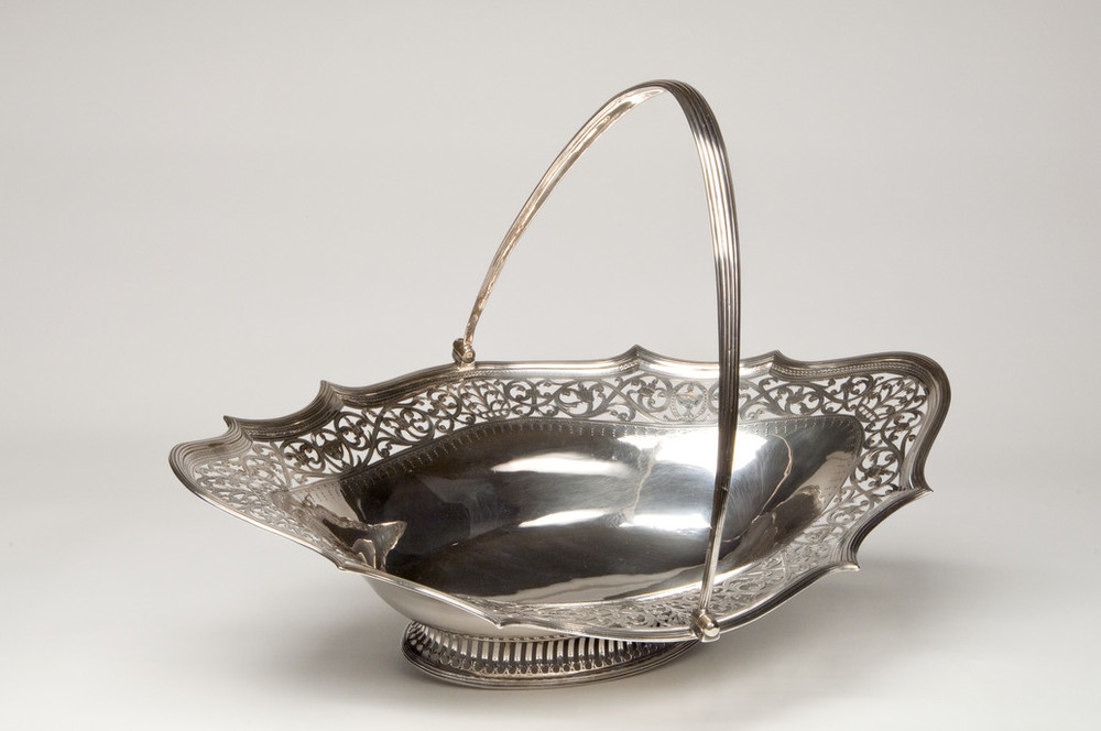 Shallow and oblong, this elegant silver cake basket features a thin, graceful handle, a wide decorative openwork border, and low neoclassical foot.