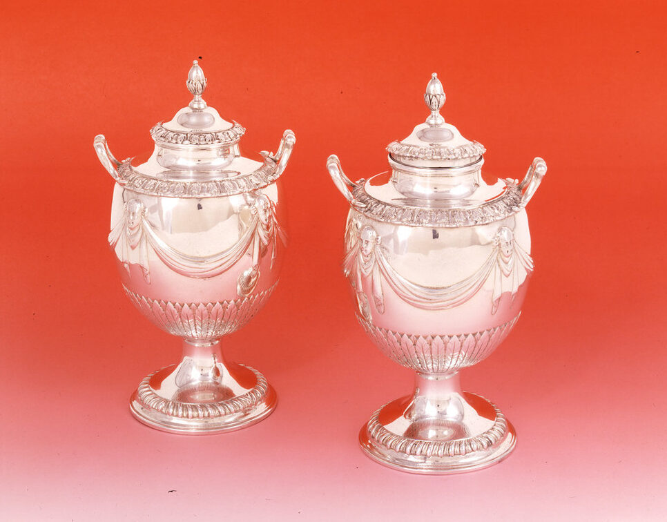 Pair of silver tea caddies with a round base, curved handles and goblet-like shape. Large swaths of polished silver are decorated with drapery punctuated by masks and narrow bands of leaflike patterns. The circular tops are decorated with an oval shape resembling an almond.