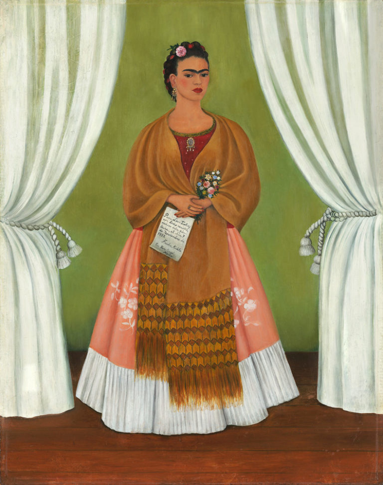The artist stands in a stage-like space framed by white curtains. Beneath black hair woven with red yarn and flowers, heavy brows accent her dark-eyed gaze. Clad in a fringed, honey-toned shawl; long, pink skirt; and gold jewelry, she holds a bouquet and a handwritten letter.