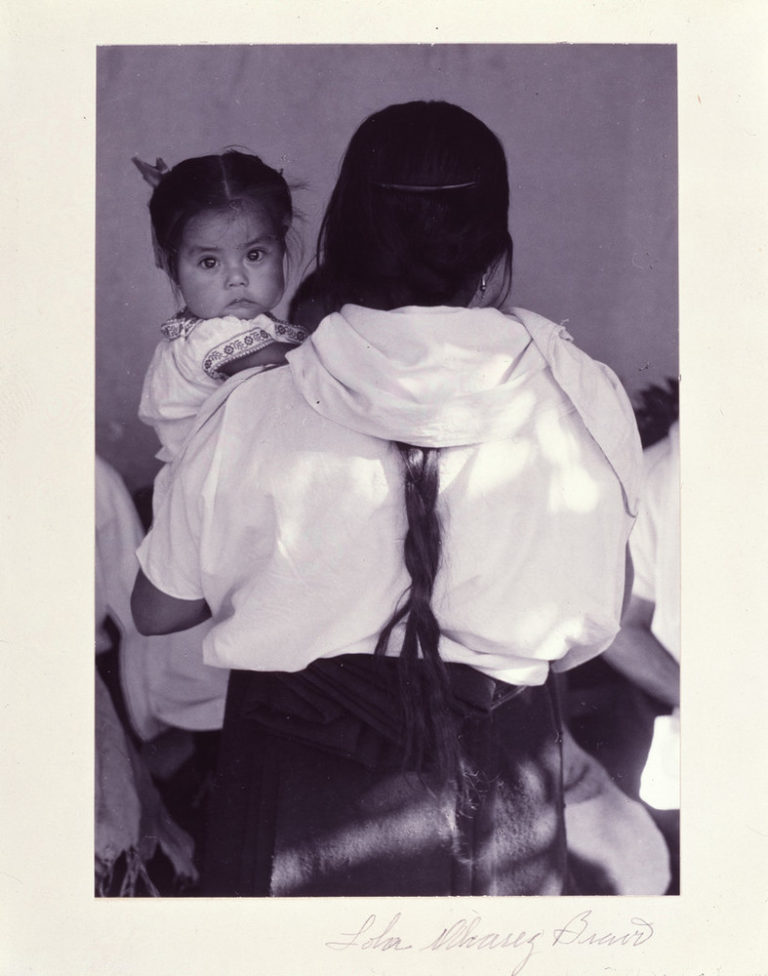 Black-and-white photograph of a woman wearing a dark skirt and light blouse holding a child. The woman faces back and her dark braid reaches past her waist. The dark-haired child stares at the camera and wears a white embroidered dress. Other figures are slightly visible beyond.