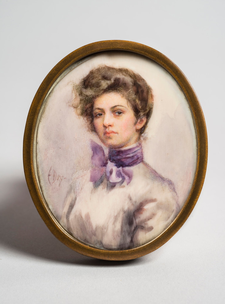 Miniature half-portrait of a light-skinned woman, set in an oval-shaped brass frame, gazing confidently at the viewer. The woman is wearing a Victorian-style white blouse with a purple scarf tied in bow around her neck, her brown hair loosely piled atop her head.