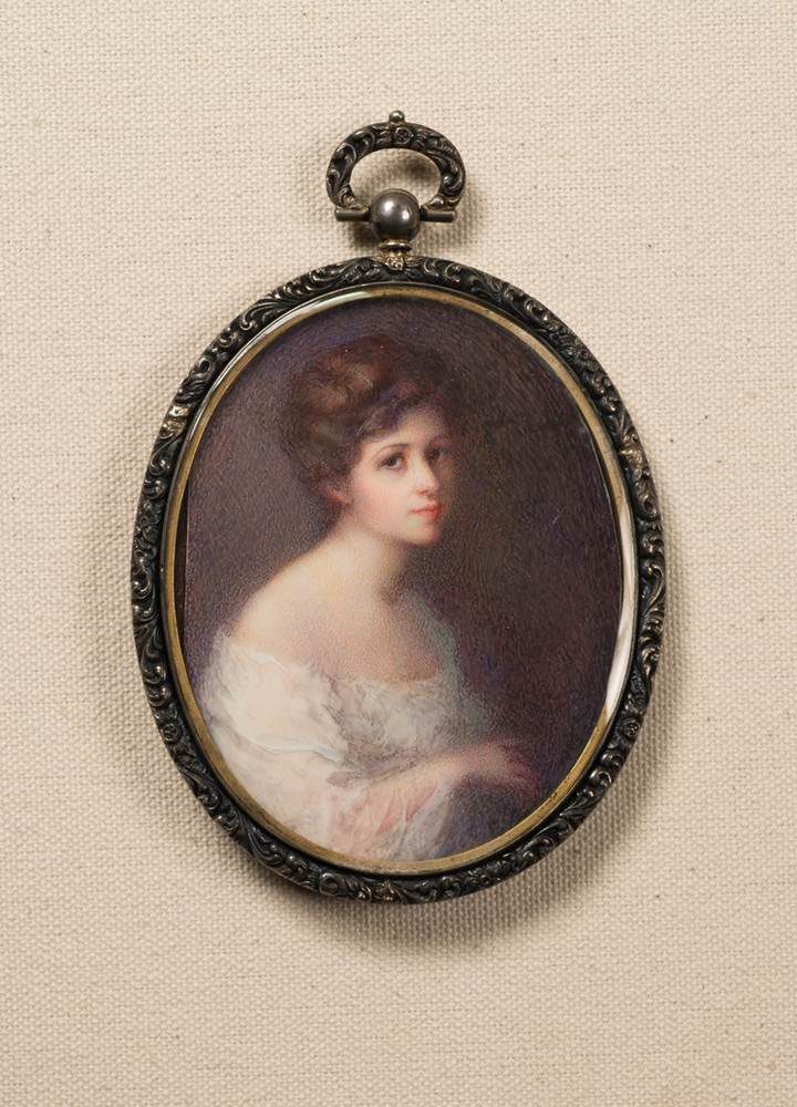 A softly painted, miniature self-portrait in an oval frame portrays the light-skinned, brunette artist against a dark background. Clad in a white, off-the-shoulder gauzy garment, she appears from the waist up, her body facing right. She turns her gaze toward the viewer.