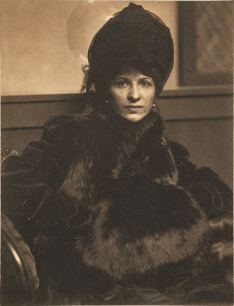 Photographic portrait of a light-skinned adult woman seated and gazing directly at the viewer. She is elegantly dressed in dark clothes and a tall, elaborate bonnet. Rich tonalities pick out the sheen of the fur muff, plush of the velvet coat, and delicate mesh of the veil.