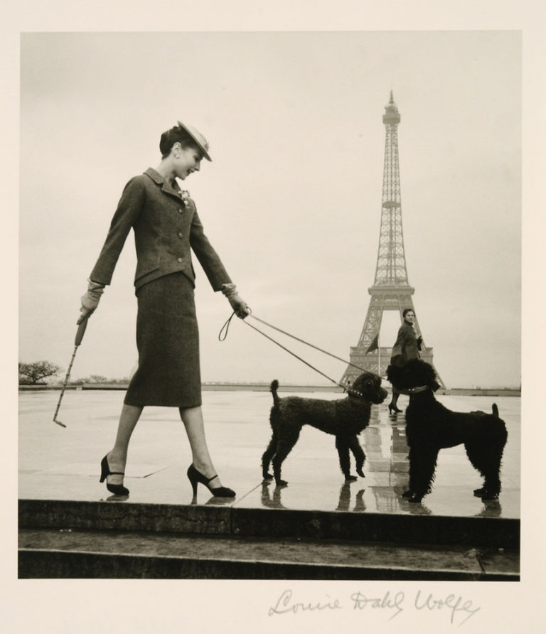 A black-and-white photograph shows a light-skinned, dark-haired woman in a rain-slick plaza with the Eiffel Tower in the distance. Posed in profile, she wears a skirt suit, hat, heels, and gloves. Her left hand holds the leads of two black poodles and her right a furled umbrella.