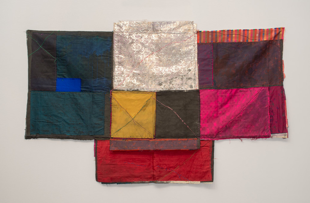 Textile collage of cloth folded and stitched together in loose geometric formations with visible seams making linear patterns. Deep blues on the left and warm colors on the right frame blocks of silver, yellow and grey in the center, which extends into a slightly longer base.
