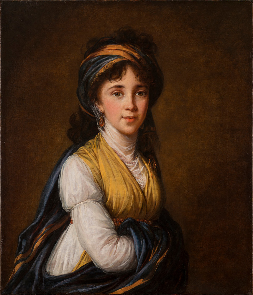 Realistically rendered half-portrait of a light-skinned young woman, gazing directly at the viewer with a faint smile on her lips. Her dark, curly hair is attractively tousled, secured under a turban-like headdress which matches her gold and blue draped ensemble.