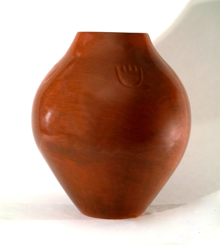 Red clay jar with a round shape that widens at its center. Its polished, warm-colored surface is decorated with a small paw print just below its top.