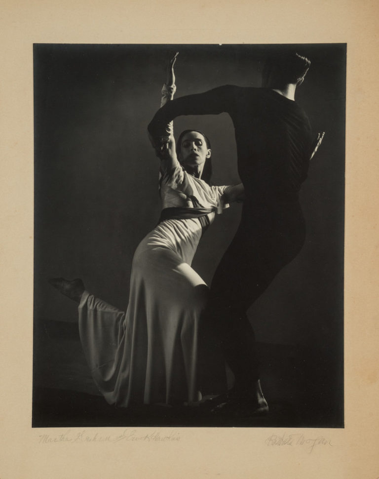 Black-and-white photograph of a man, dressed in black, and Martha Graham, in white, dancing. Graham, lit from above, strikes one of her famous angular poses, both legs bent, the back foot pointing behind her. Her raised arms are held by the man, who stands with his back to us.