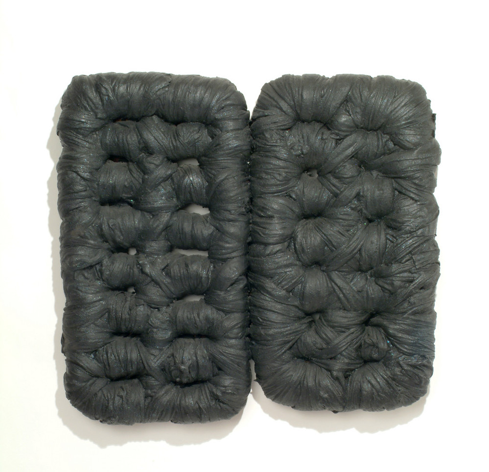 Wall sculpture featuring two rounded rectangular forms, the right slightly smaller than the left, resembling tufted cushions. The forms perimeters and interior sections are wrapped in fabric heavily coated with matte black latex paint, accentuating the tufts and folds of the fabric.