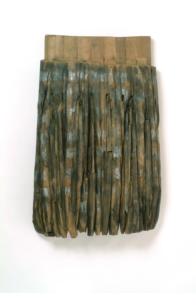 Resembling the pleats and band of an apron, this large, one-sided, cedar sculpture features carved vertical lines darkened with graphite and stain beneath a solid band of natural-colored wood.