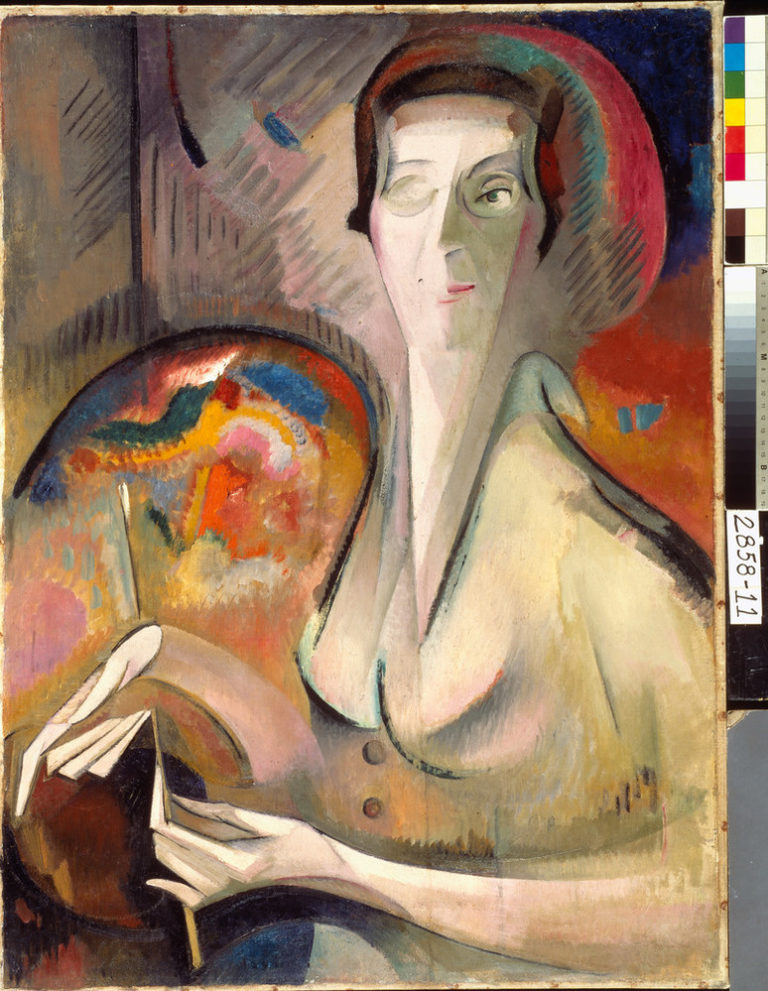 Dynamic painting features a backdrop of red, orange, and blue hues. The artist's face, hands, and body are composed of conjoined geometric and organic shapes in a neutral color palette. Her left eye and hands are explicitly described, as is artist's palette on her right.