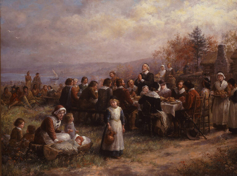 """A detailed painting portrays an idealized version of the """"First Thanksgiving."""" At right, austerely garbed men and women and one Native American sit at a long table as an old man leads a prayer. A woman attends small children at the left, and group of Native Americans sits nearby."""