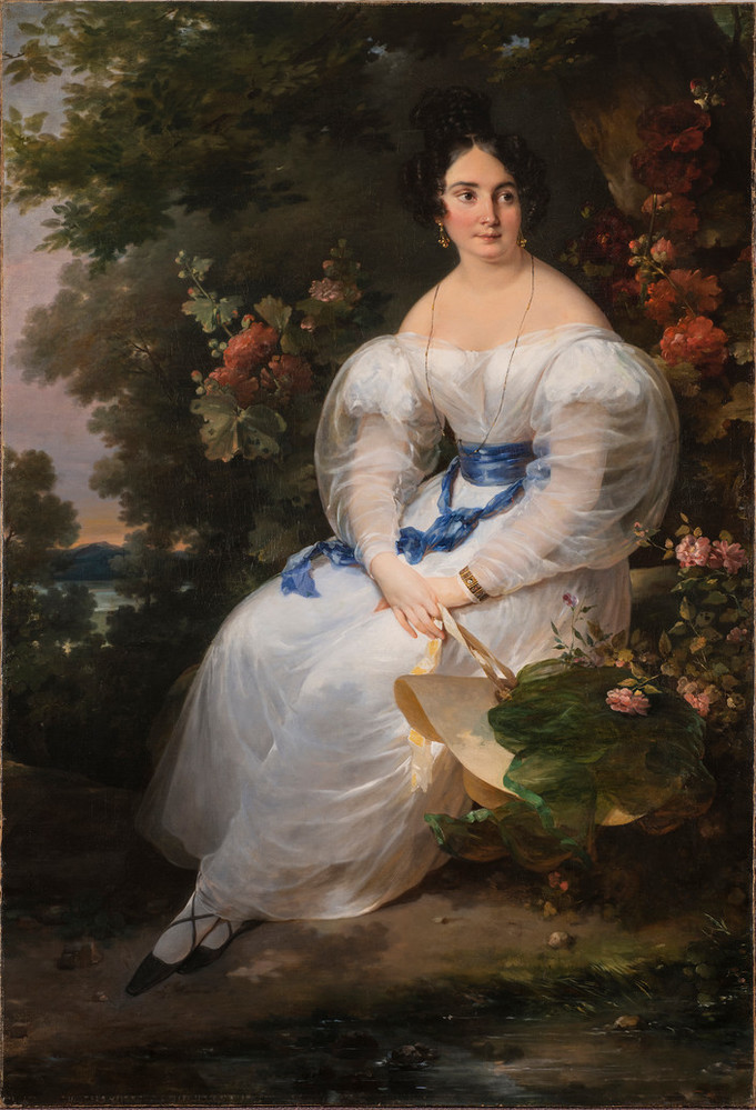 Full-length portrait of a light-skinned woman with black hair pinned up, gazing off to the viewer's right. She wears a delicate white gown with billowing sleeves and blue silk sash and holds a straw sun hat in front of a large dark tree surrounded by flowering bushes.