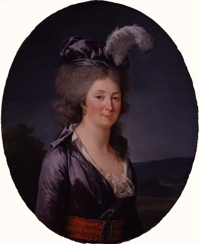 A light-skinned woman with grey hair stands in front of a dark landscape. She smiles slightly, wearing a blue dress with long sleeves, white lace, and a brown belt with a dark buckle. A large white feather perches on her blue hat, a gold earring hangs from her right ear.