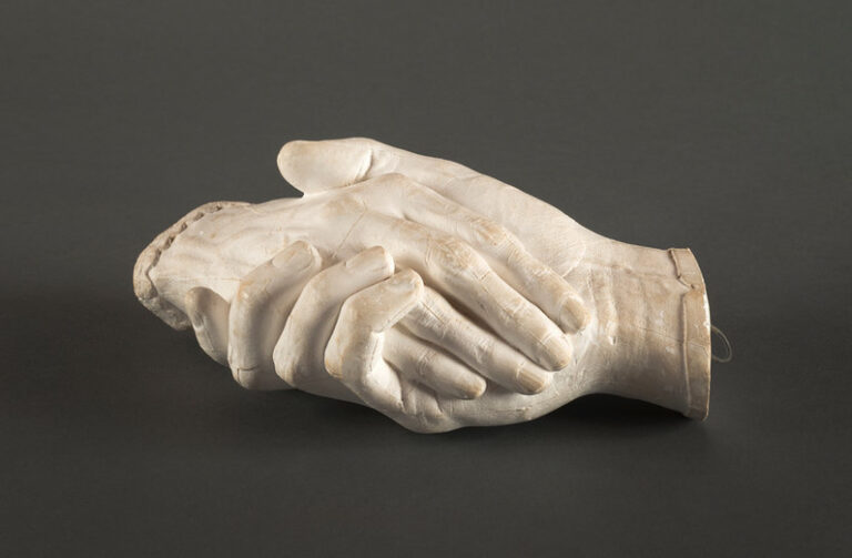 Life-sized plaster cast sculpture of a man's hand on the bottom holding a woman's hand on top. The matte white surface reveals the textures of the skin and fingernails. The man's hand is capped with a plain thin cuff, while the woman's is capped with a delicate lace cuff.