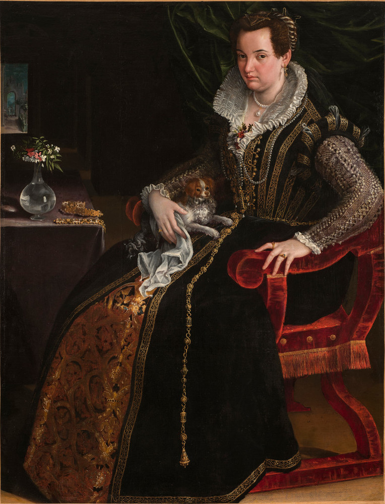 A light-skinned, dark-haired woman wearing pearl and gold jewelry and a black-velvet, lace, and brocade gown poses with her lap dog. Seated in a red velvet chair in the foreground, she makes eye contact with viewers while pressing her hand on the armrest, as if to stand.