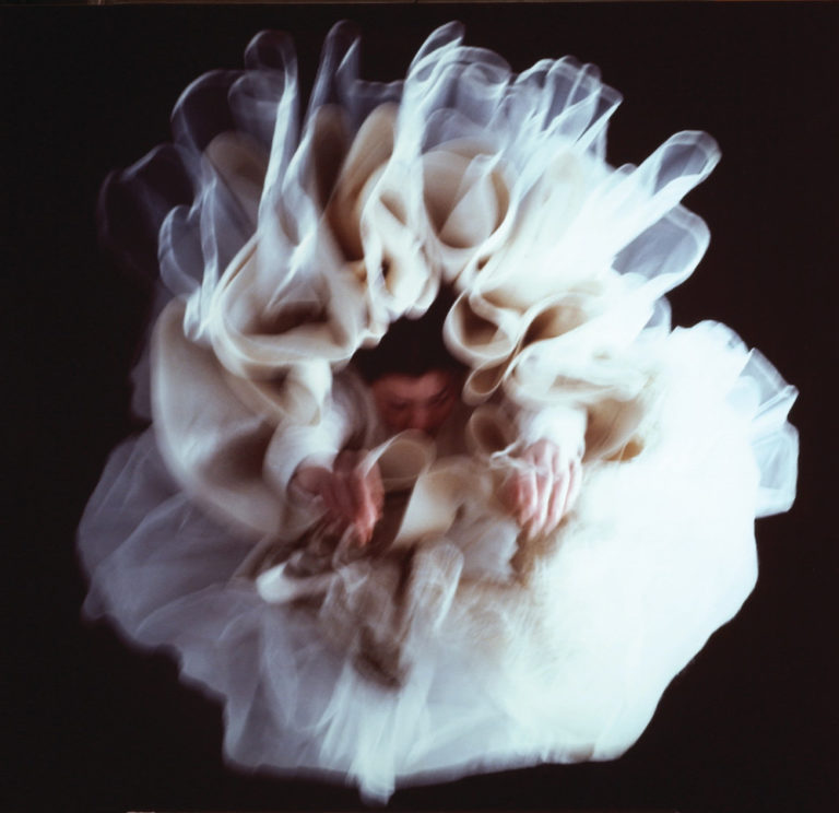 Large, glossy, blurry, color photograph of a light-skinned woman hanging upside-down directly above the viewer. Her arms hang loosely above her head, enveloped in diaphanous white skirts billowing around her, set against a black background, creating a flower-like appearance.