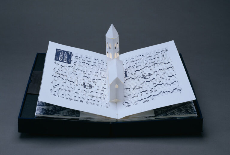 Bound in a dark blue fabric-covered binding, the book opens to display five pop-up towers illuminated from within by a tiny bulb. The featured page includes a white country church with a steeple, set into pages featuring musical scores presented in manuscript style.