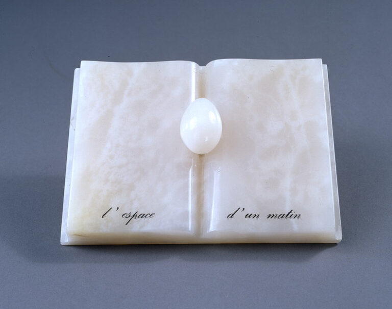 An open book with an egg nestled in the spine, all made of rose-colored onyx. An inscription in French painted in black at the bottom reads,