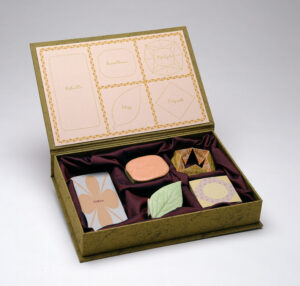 """A green-gold box with its attached lid flipped open holds five objects shaped liked candies resting on burgundy fabric. The inside of the lid displays outlines of each object, with the words """"life cycle,"""" """"labyrinth,"""" """"elegy,"""" """"either/or,"""" and """"social graces"""" inside the outlines."""
