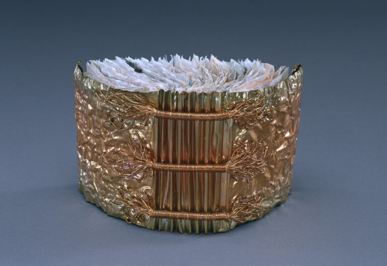 A book whose cover is made of copper is open and standing upright with its spine facing viewer. Three horizontal bands of wound copper wire extend the width of the accordion pleated spine. Crumpled paper comprises the pages of the book.