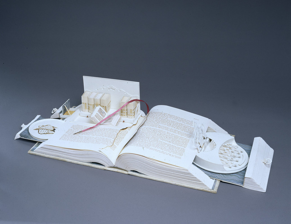 A white book opens like a Swiss army knife; its pages cut to create a sculpture. Opened to the center, pull-out drawers open from the sides, filled with paper-made objects. On the right, a typewriter-like object. On the left, a box with smaller books, including one that is also open.