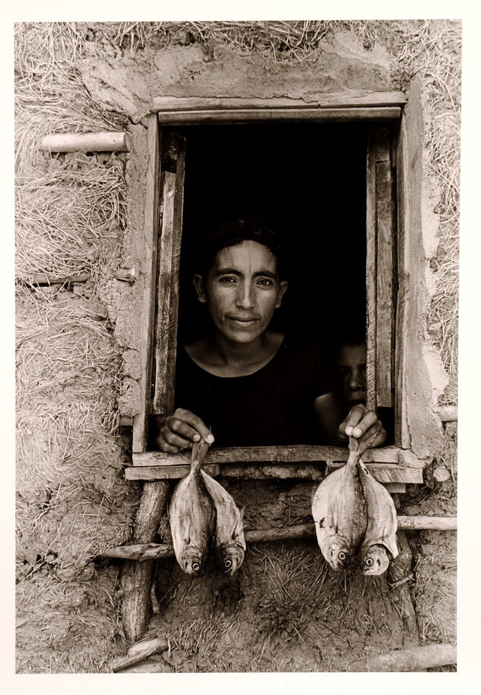 A black-and-white photograph features an open, rough-hewn window framing the head and shoulders of a woman with dark hair and medium-dark skin. Peering out from a murky interior, she displays 2 fish per hand on the window ledge. A mud-grass mixture textures surrounding walls