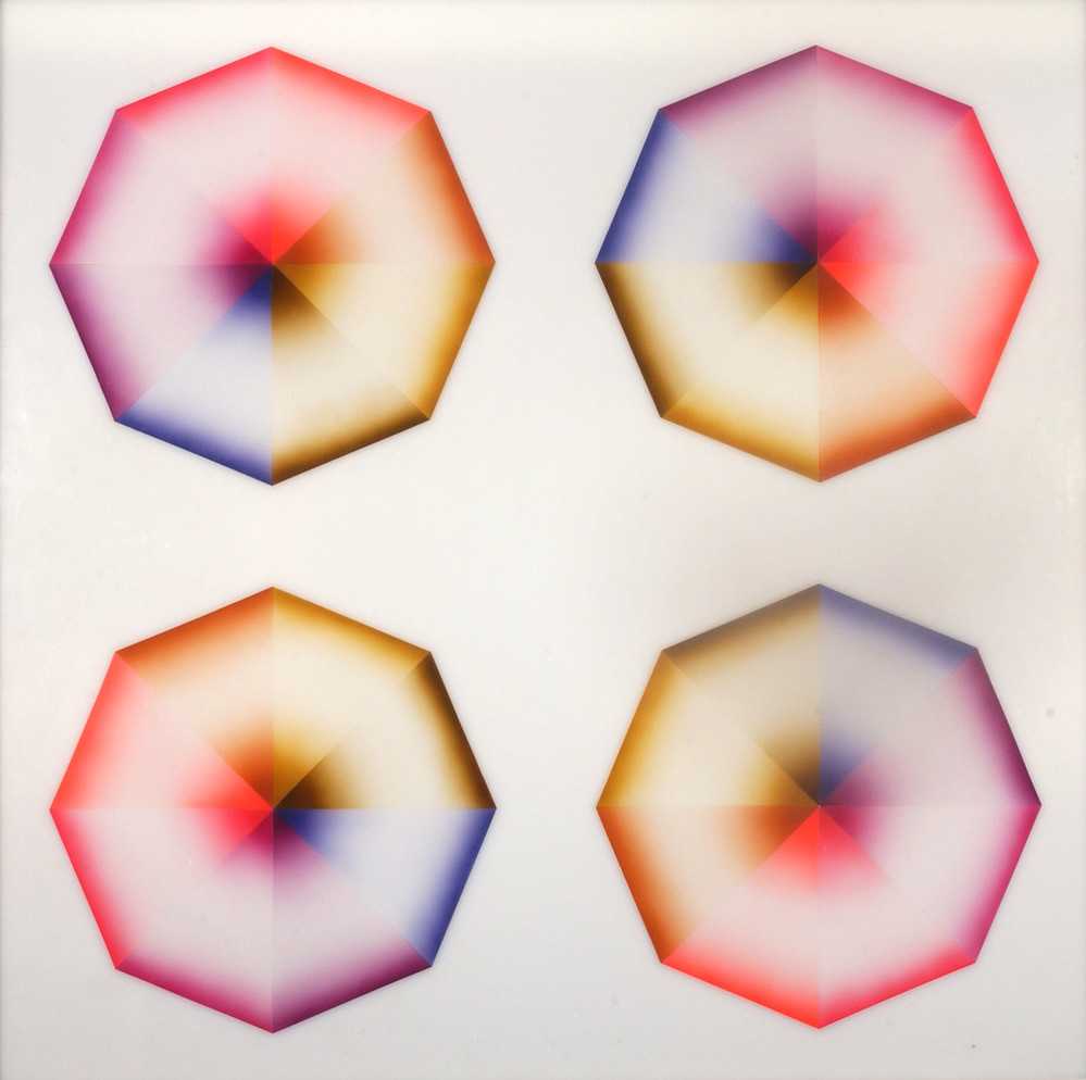 Four hard-edged octagons, each divided into eight pie-slice shapes painted red, pink, orange, yellow, olive green, blue, violet, or lavender, occupy a square, white background. Dark at the wide and narrow ends of each wedge, the hues create the illusion of 3-dimensional forms.