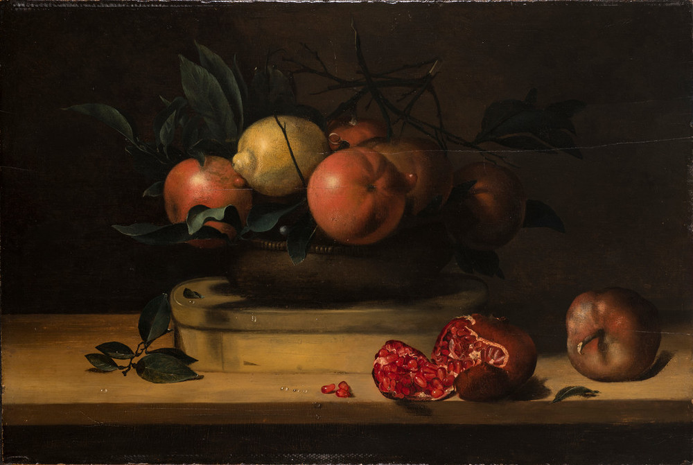 A vessel mounded with 5 oranges, a lemon, and greenery sits atop an oval, wooden box resting on a wooden plank. In the foreground, two pomegranates, one of which has split open and dropped three seeds, balance near the plank's edge. Droplets of water dot the fruit and the table.