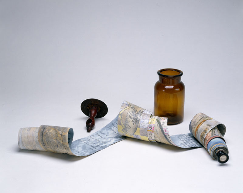 A small antique amber jar and a wooden scroll holder are arranged alongside a long scrolled paper with handwriting on one side and the faint hint of collaged sewing patterns, maps, and newsprint on the reverse side.