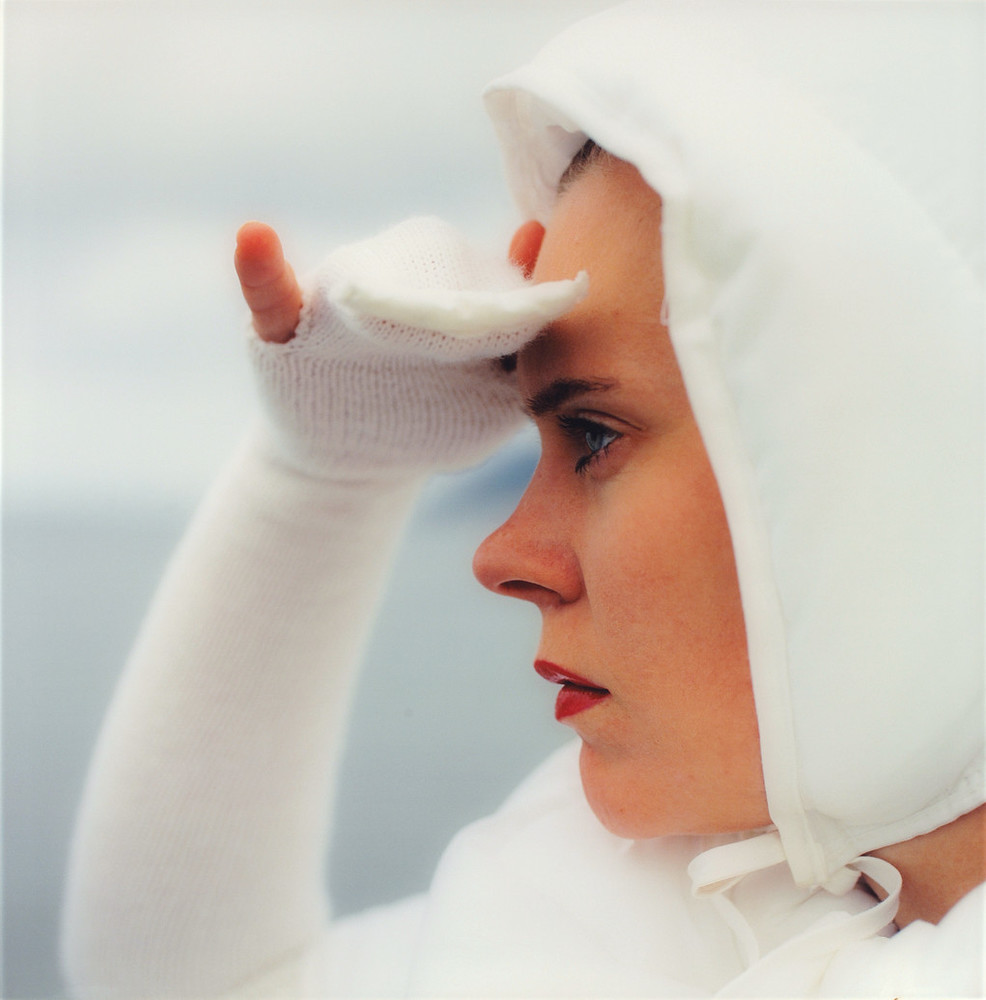 Close-up of a woman in profile looking to the left. She is wearing all white including a bonnet and she is holding her hand up as if to shield her eyes from the sun.