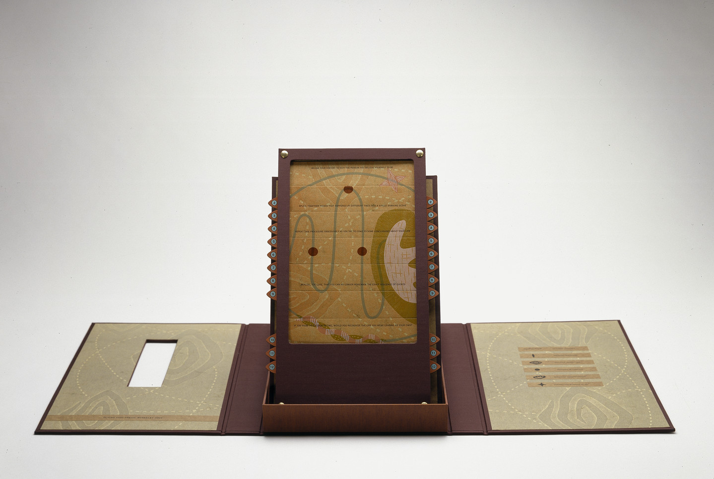 An open maroon portfolio with contents displayed upright in center. Upright panel is an abstract image with red circles connected by a curving green line on a mustard yellow background.