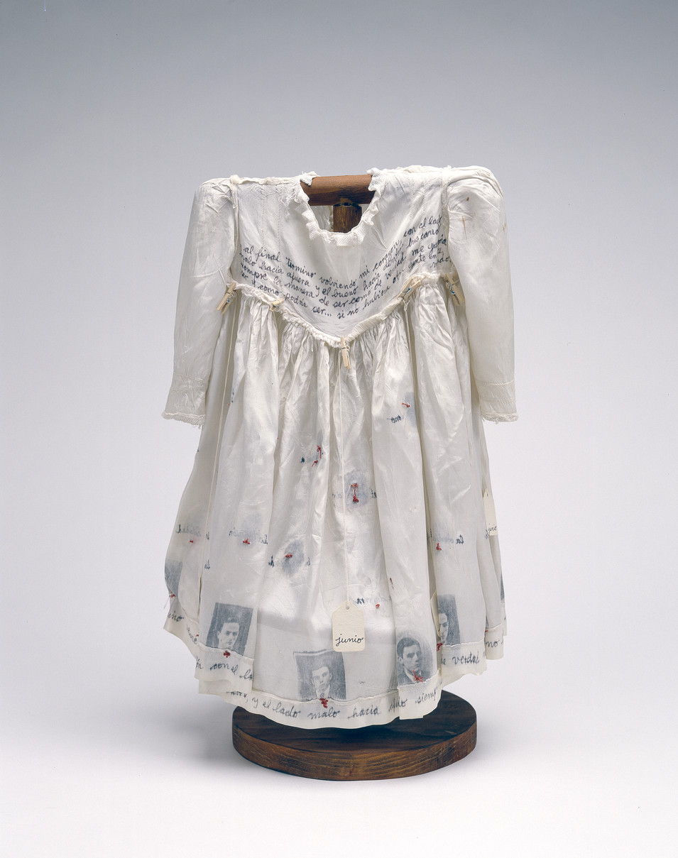 Hung on a dark wood, T-shaped form, a child's ivory-colored silk dress serves as a canvas for photographs, calligraphy, stitching, and the words of Anne Frank.