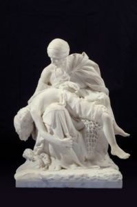 Large sculpture in white marble depicts a seated older woman cradling the body of a young boy whose limp body falls over her legs. The boy's legs are tangled in a fisherman's net while waves crash at the woman's feet.