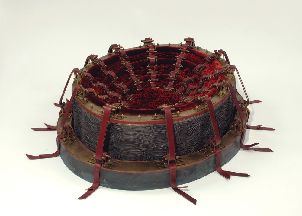An oval, vessel-shaped sculpture features a concave interior of concentric, ruby-red velvet folds. Twelve evenly spaced, red leather straps adorned with brass hardware radiate from the center. They appear to restrain the interior and anchor the piece to the floor.