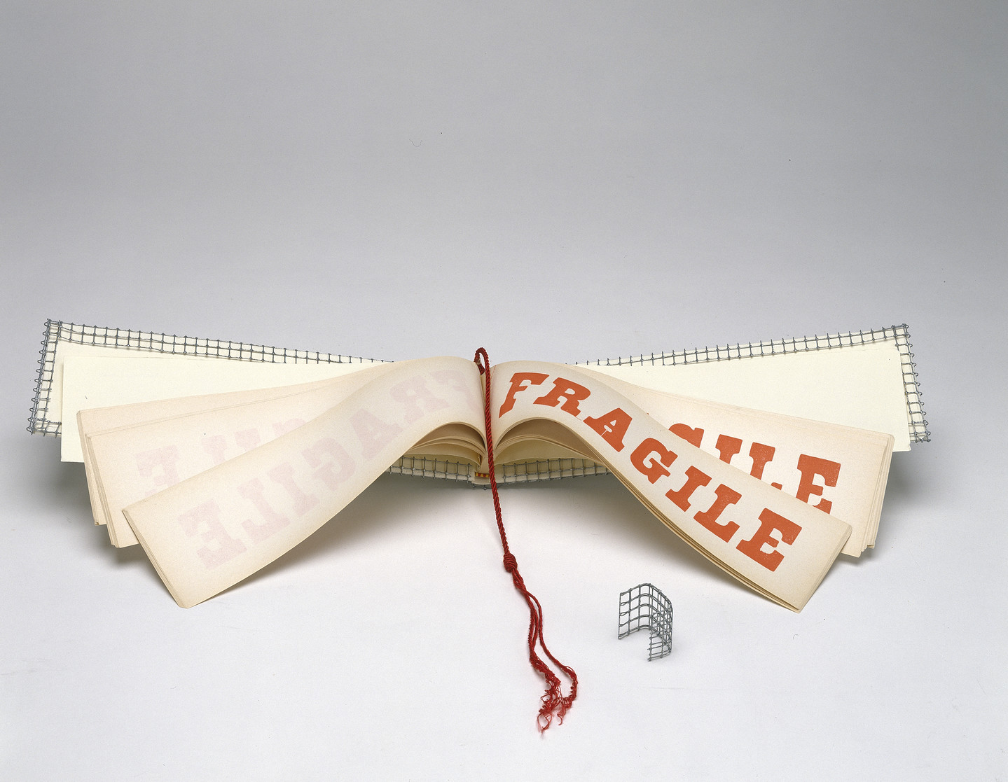 A wide and narrow book opened to display pages with the word FRAGILE in red block letters. A red tassle hangs down the center of the book and the cover is wrapped with wire mesh.